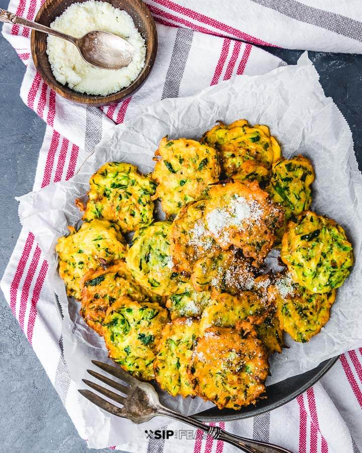 Plate of zucchini fritters on towels with bowl of cheese on the side.