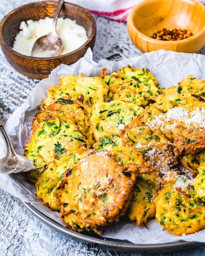 Zucchini fritters in large plate with bowl of Pecorino Romano cheese and crushed red pepper flakes in background.