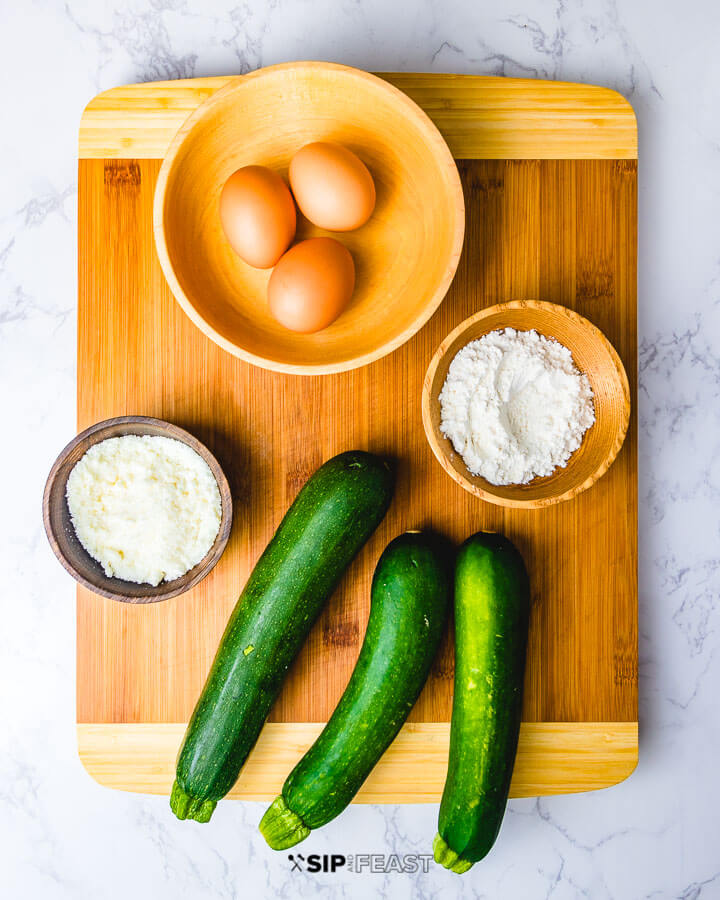 Ingredients shown: eggs in bowl, flour in bowl, cheese in bowl and 3 zucchini.