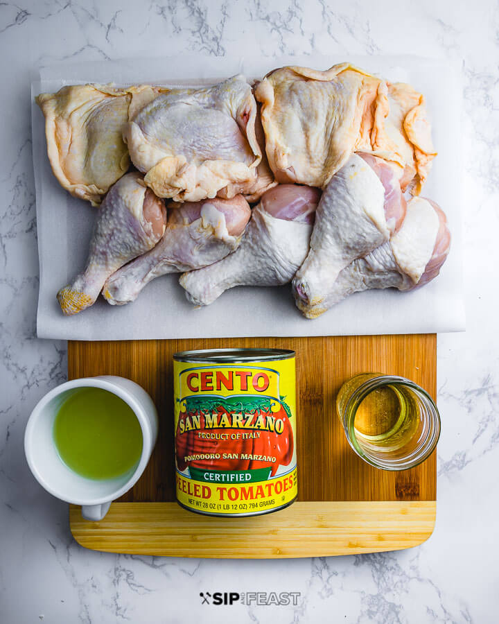 Ingredients on cutting board: chicken pieces, chicken stock, canned plum tomatoes, and white wine.