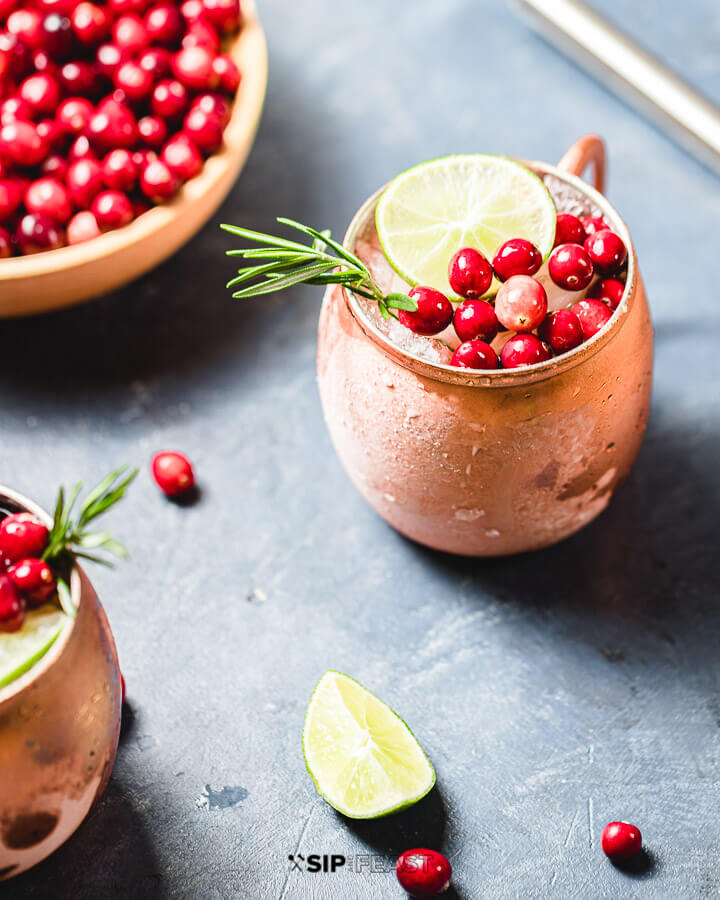 Bowl of cranberries and two copper mugs filled with the Cranberry Moscow Mule.