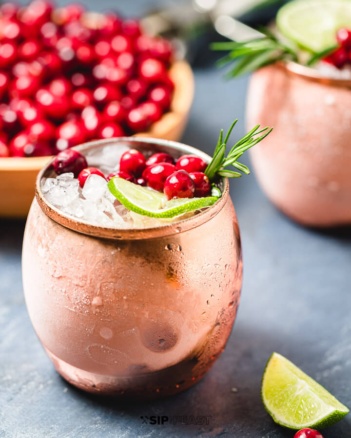 Two copper mugs with the Cranberry Moscow Mule cocktail, and a bowl of cranberries.