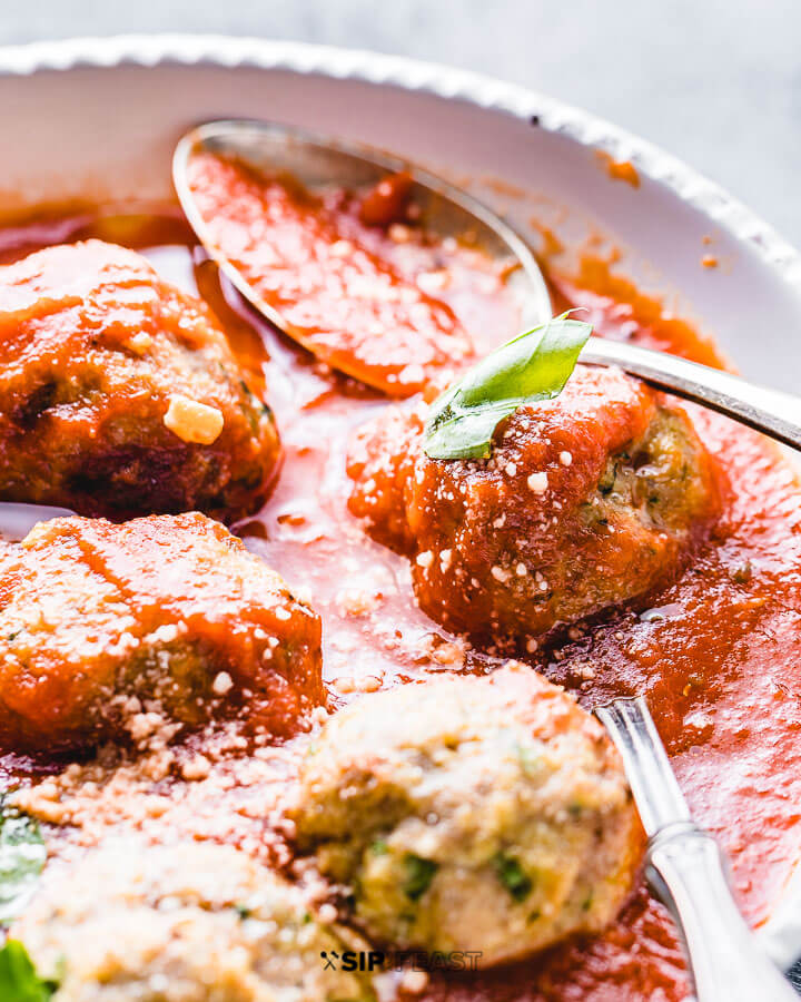 Turkey meatballs with red sauce in a white bowl.
