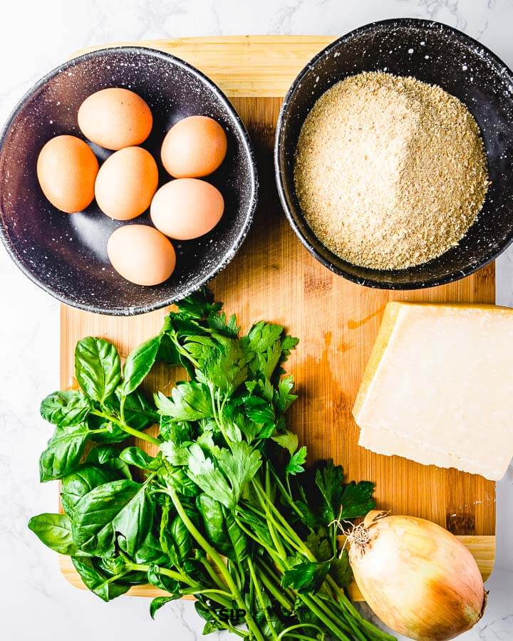 Ingredients shown: eggs, breadcrumbs, basil, parmesan cheese, and a large onion.