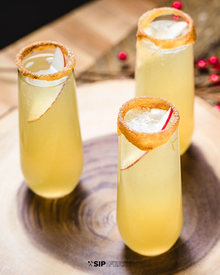 3 caramel apple mimosas in stemless champagne flutes garnished with a rim of caramel, sugar and cinnamon, and one slice of apple.