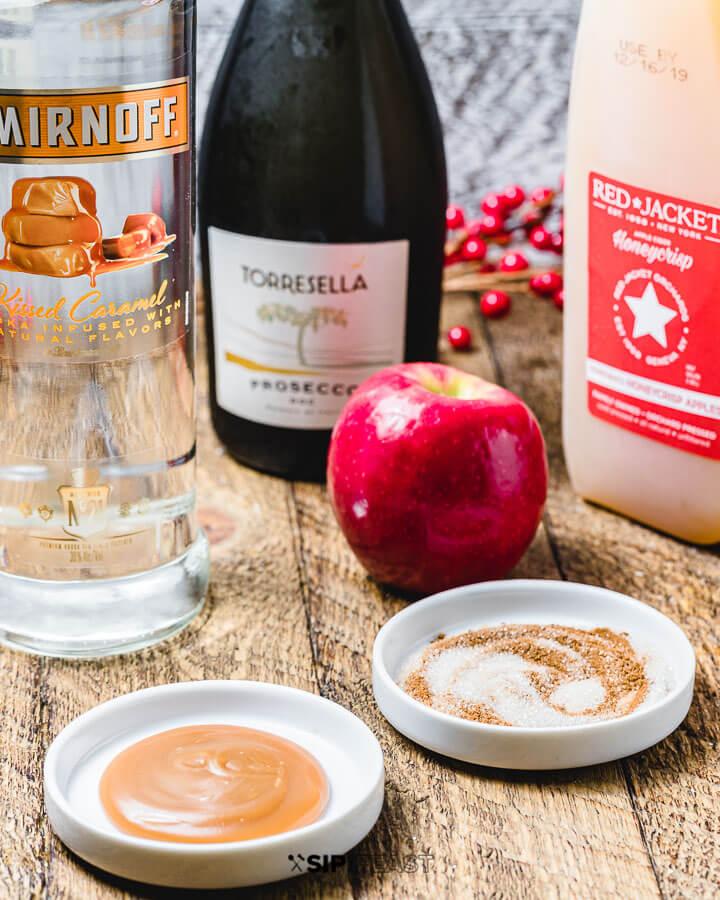 Ingredients shown: prosecco, caramel vodka, apple cider, caramel sauce, cinnamon/sugar and apple.