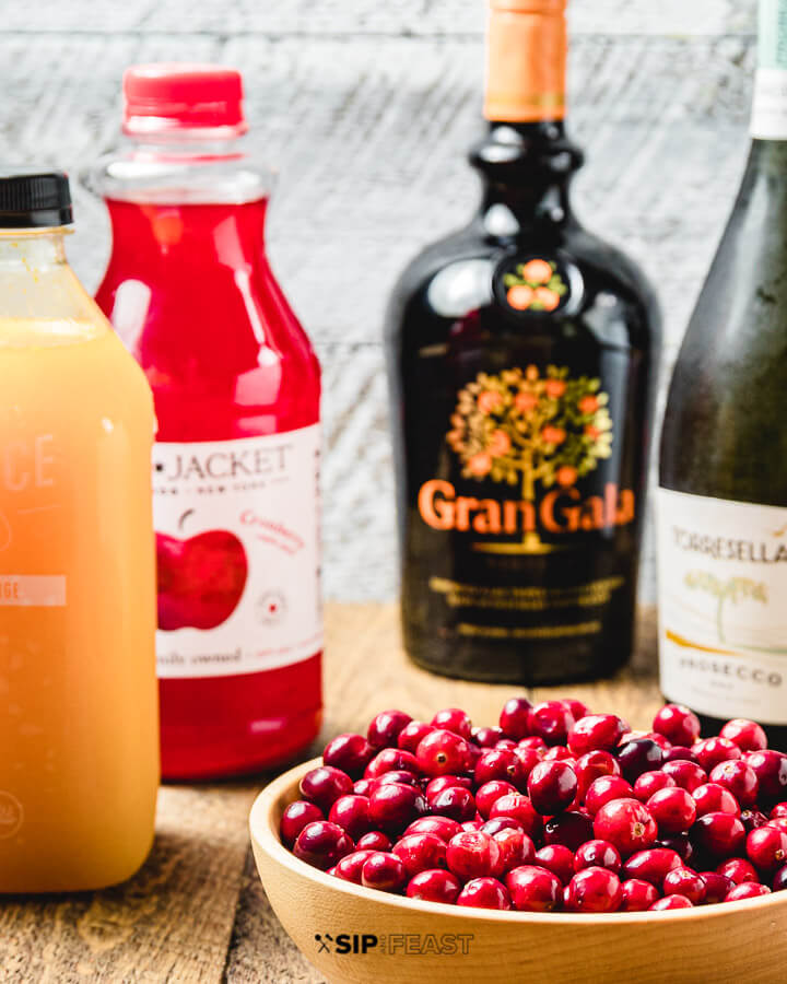 Ingredients shown: orange Juice, cranberry juice, Gran Gala, prosecco, and bowl of cranberries.
