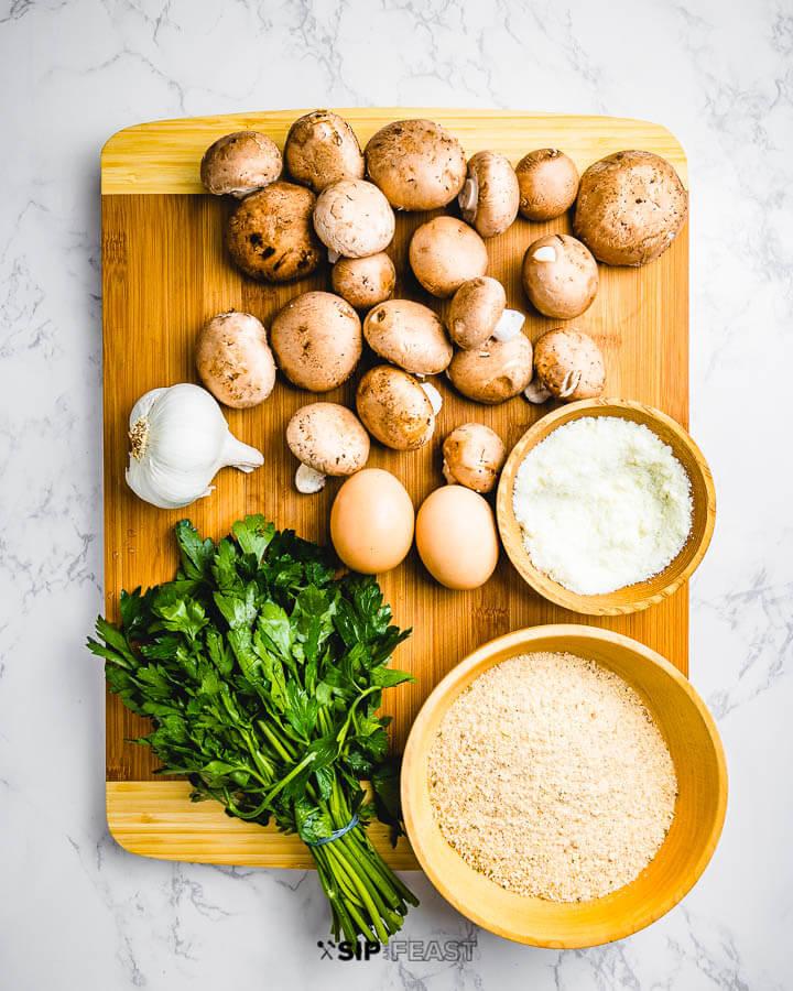 Ingredients shown: baby Bella mushrooms, garlic, Pecorino Romano cheese, parsley, and breadcrumbs.