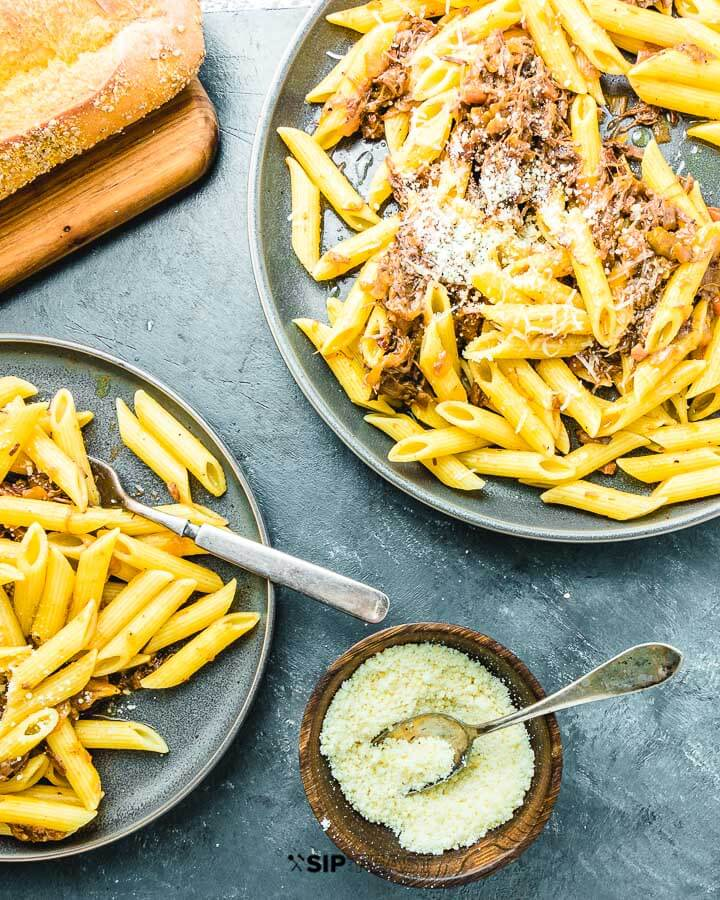 Two plates of Penne Alla Genovese with grated cheese and bread on blue background.