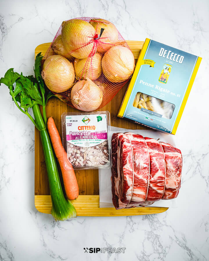 Ingredients shown: onions, penne pasta, celery, carrots, pancetta, and a chuck roast.