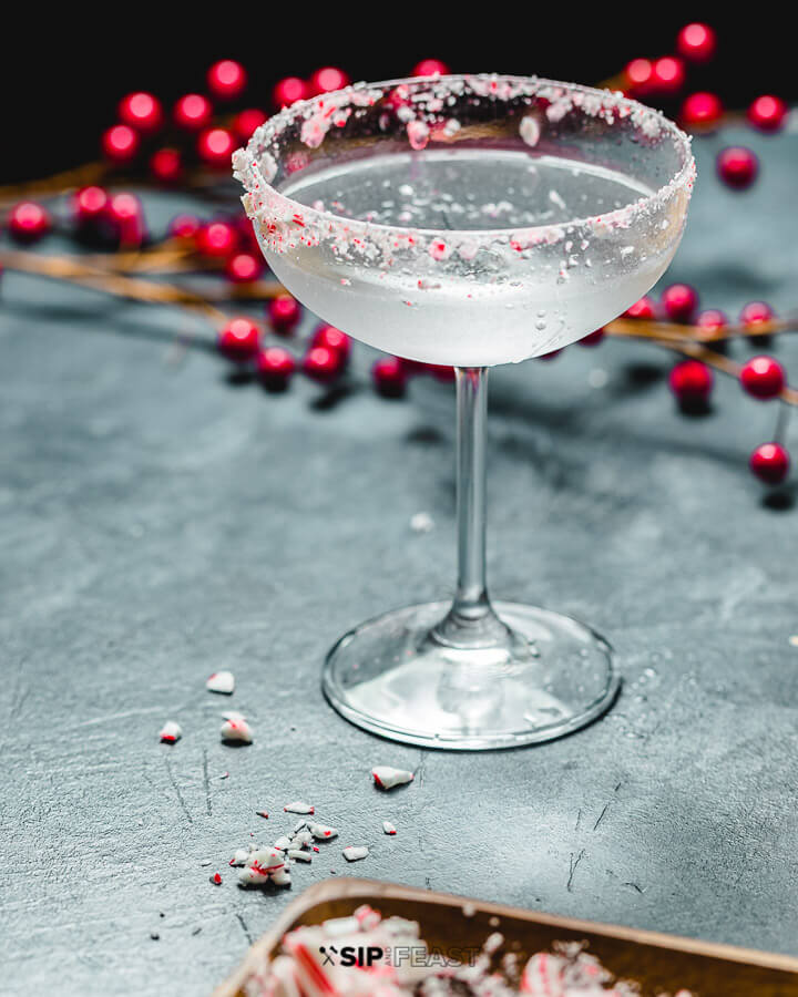 Candy Cane cocktail with berries and crushed candy cane powder.