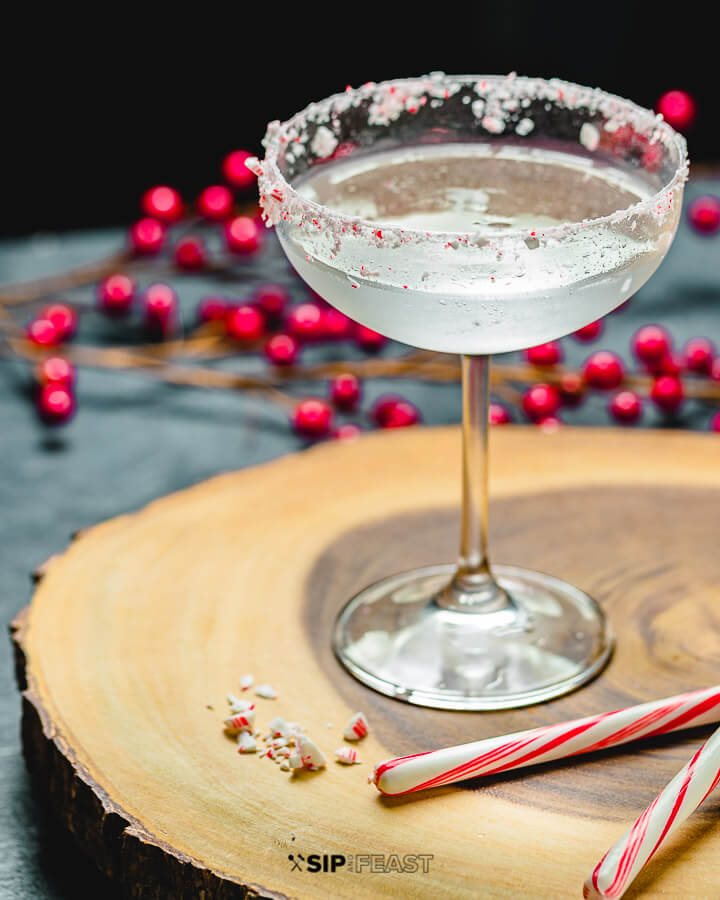 Candy Cane Cocktail with holly berries and candy canes in background