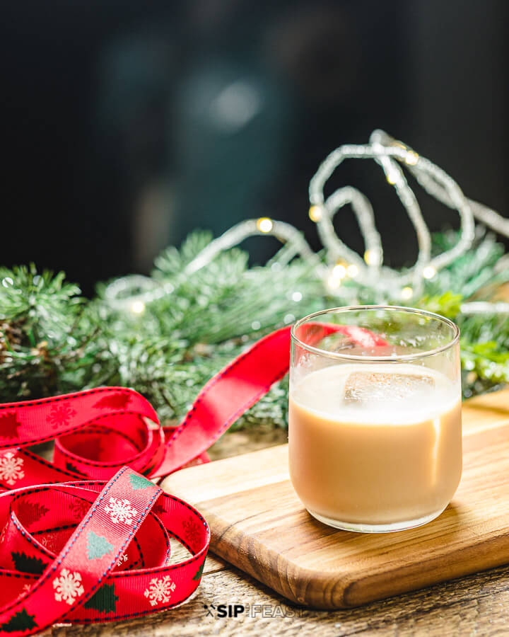 Glass of eggnog white Russian with ribbon, pine leaves and lights.