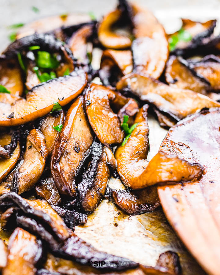 Sliced portobello mushrooms in pan.