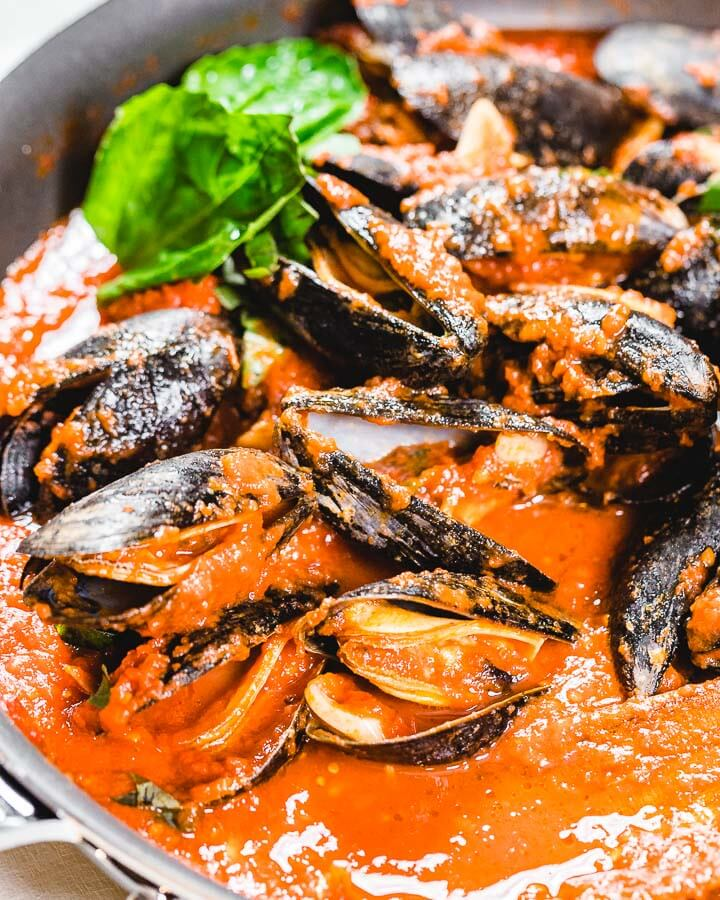 Pan with mussels in the marinara sauce with basil in background.