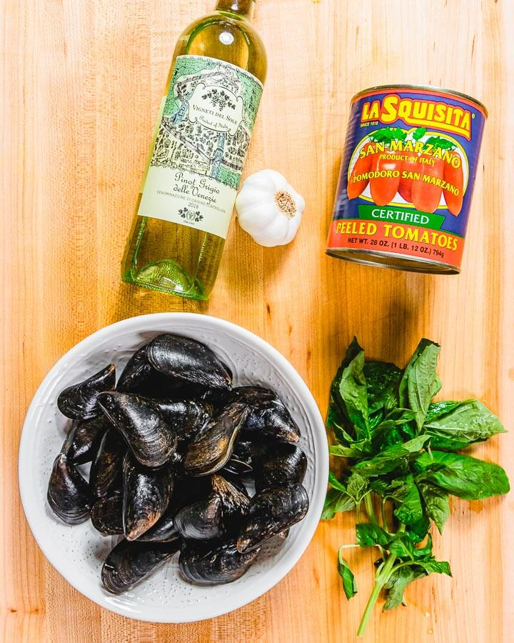 Ingredients shown: white wine, one can plum tomatoes, garlic, mussels, and basil.