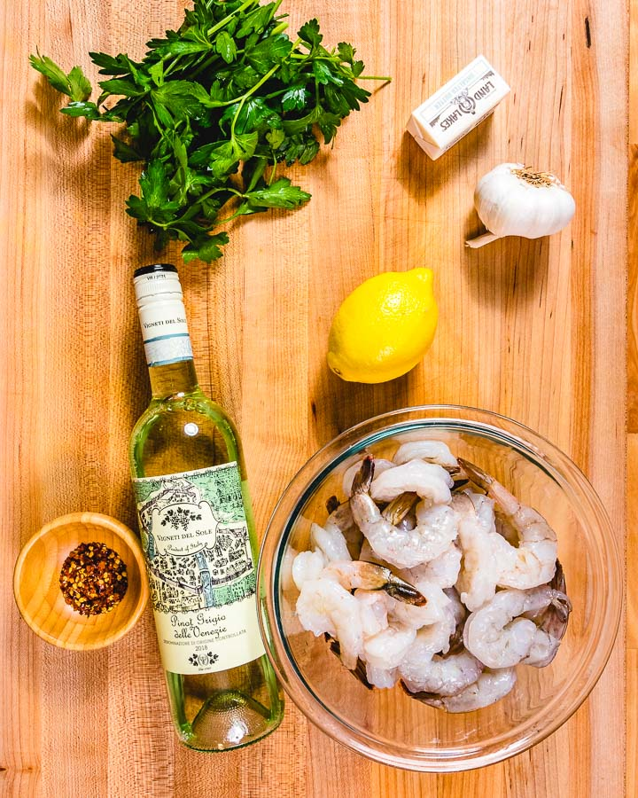 Ingredients shown on cutting board: parsley, butter, lemon, garlic, white wine, and shrimp in glass bowl.