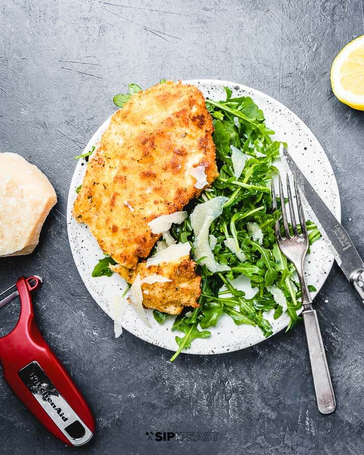 Chicken Milanese in white plate with lemon and parmesan cheese on the side.