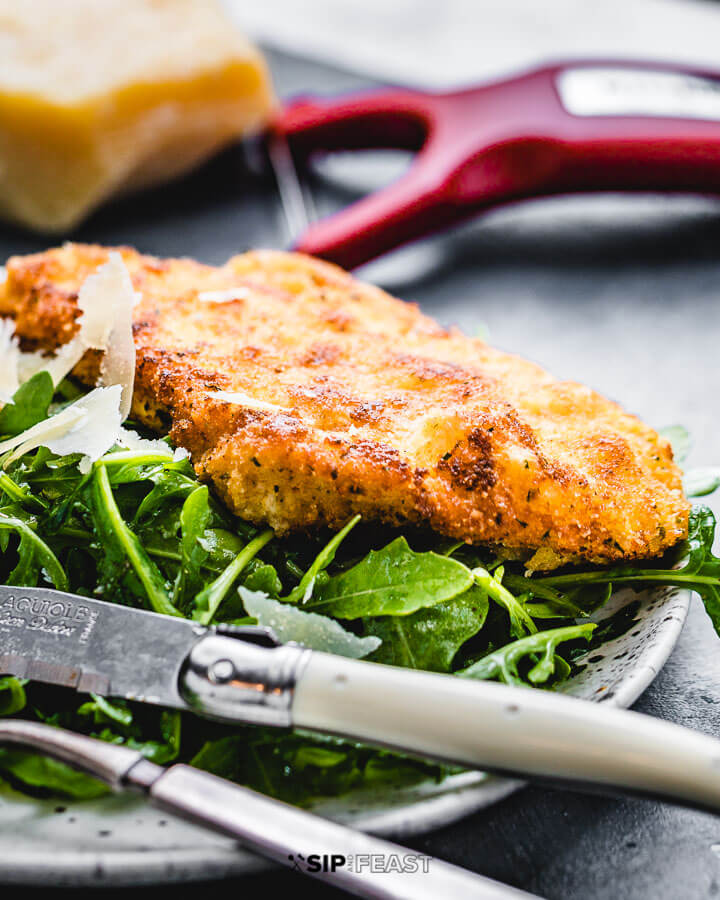 Italian chicken cutlet on top of arugula salad in white plate.