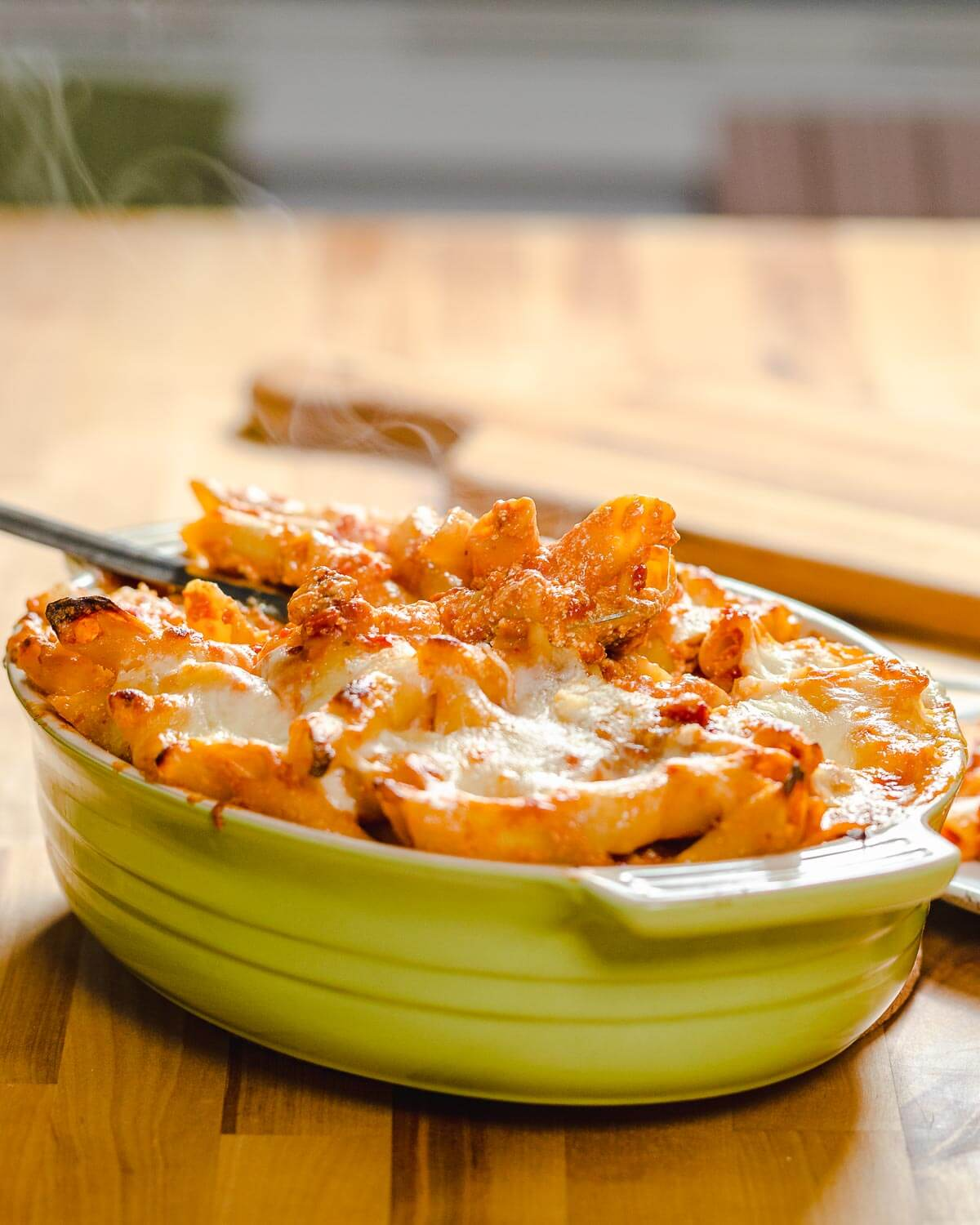 Baked pasta dish on table with steam rising from it.