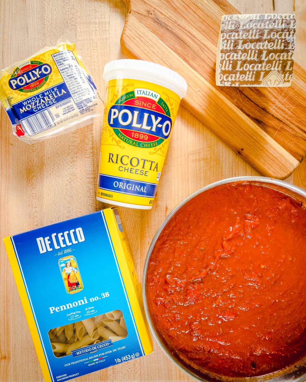 Ingredients shown: Pecorino Romano, mozzarella, ricotta cheese, pasta, and a pot of sauce.