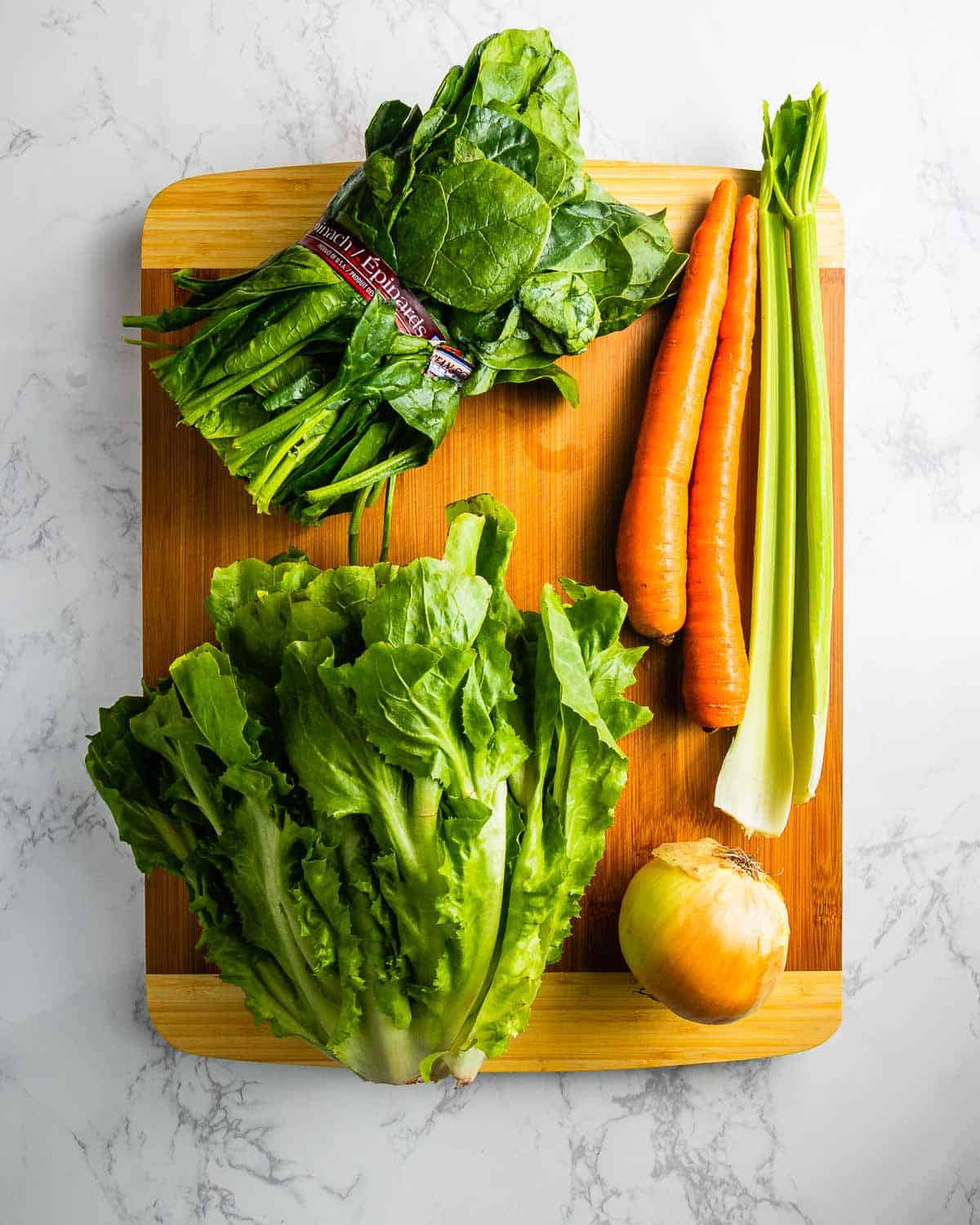 Escarole, spinach, carrots, onion, and celery on cutting board.