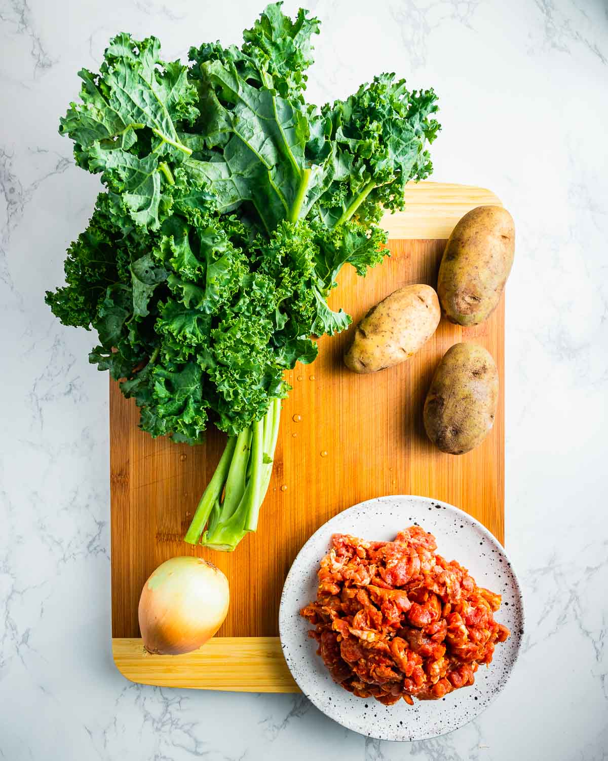 Ingredients shown: Tuscan kale, potatoes, onion, and spicy sausage removed from casing.
