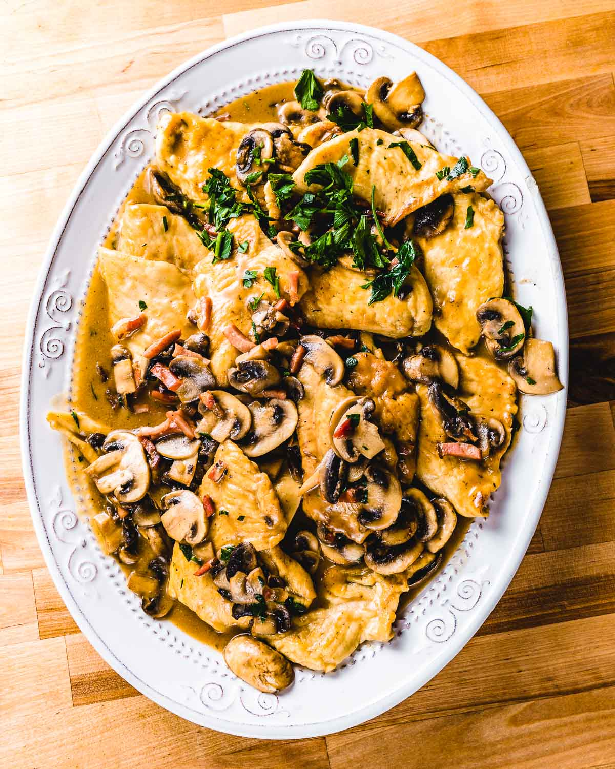 Large white plate of chicken marsala on wood table.