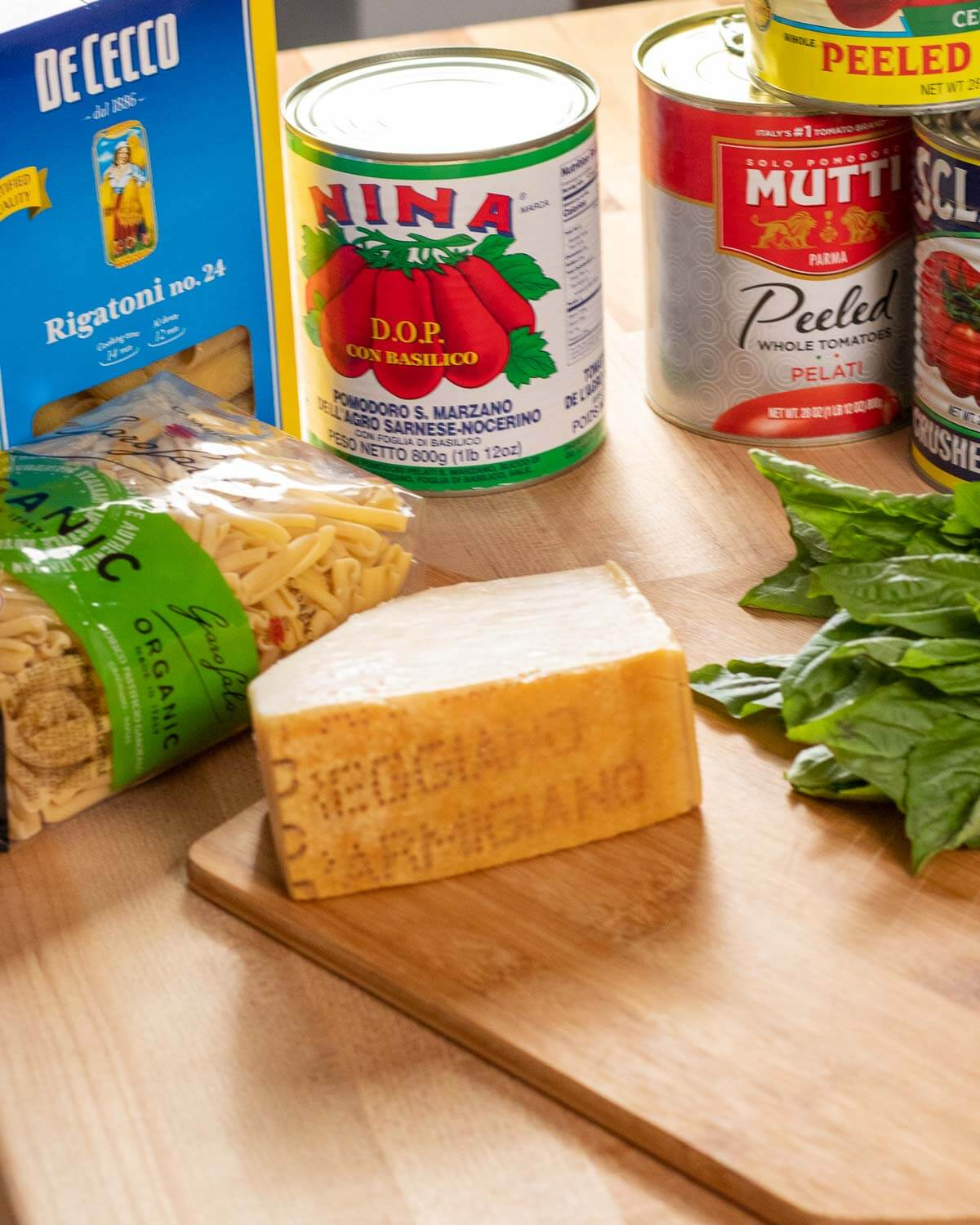 Ingredients shown: rigatoni and casarecce pasta, 4 cans of plum tomatoes, basil, and block of parmesan cheese.
