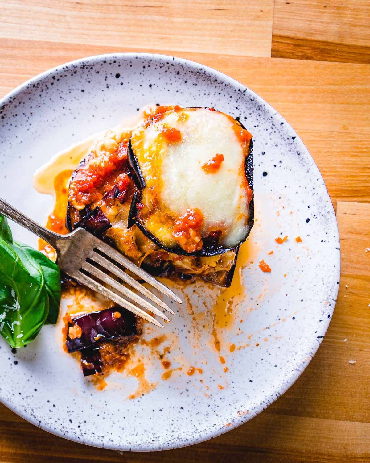 One serving of eggplant parm in white plate with fork on table.