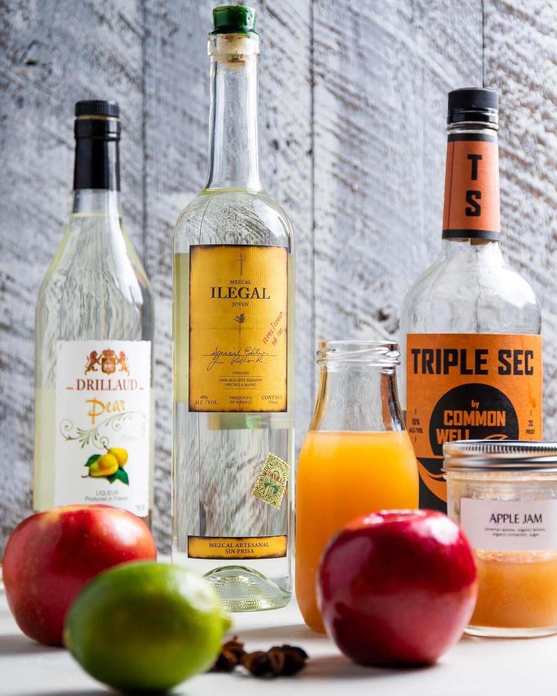 Ingredients shown: pear liqueur, mezcal, triple sec, apple cider, apple jam, apples, and lime.