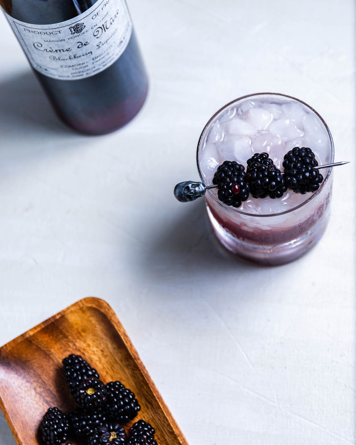 Overhead shot of Blackberry Bramble with Creme de Mure bottle and plate of blackberries.