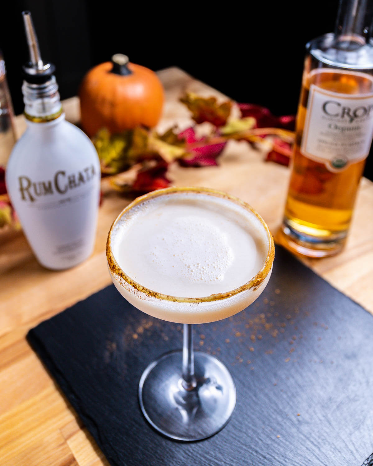 Pumpkin spice martini on table along with bottle of Rum Chata and pumpkin vodka.