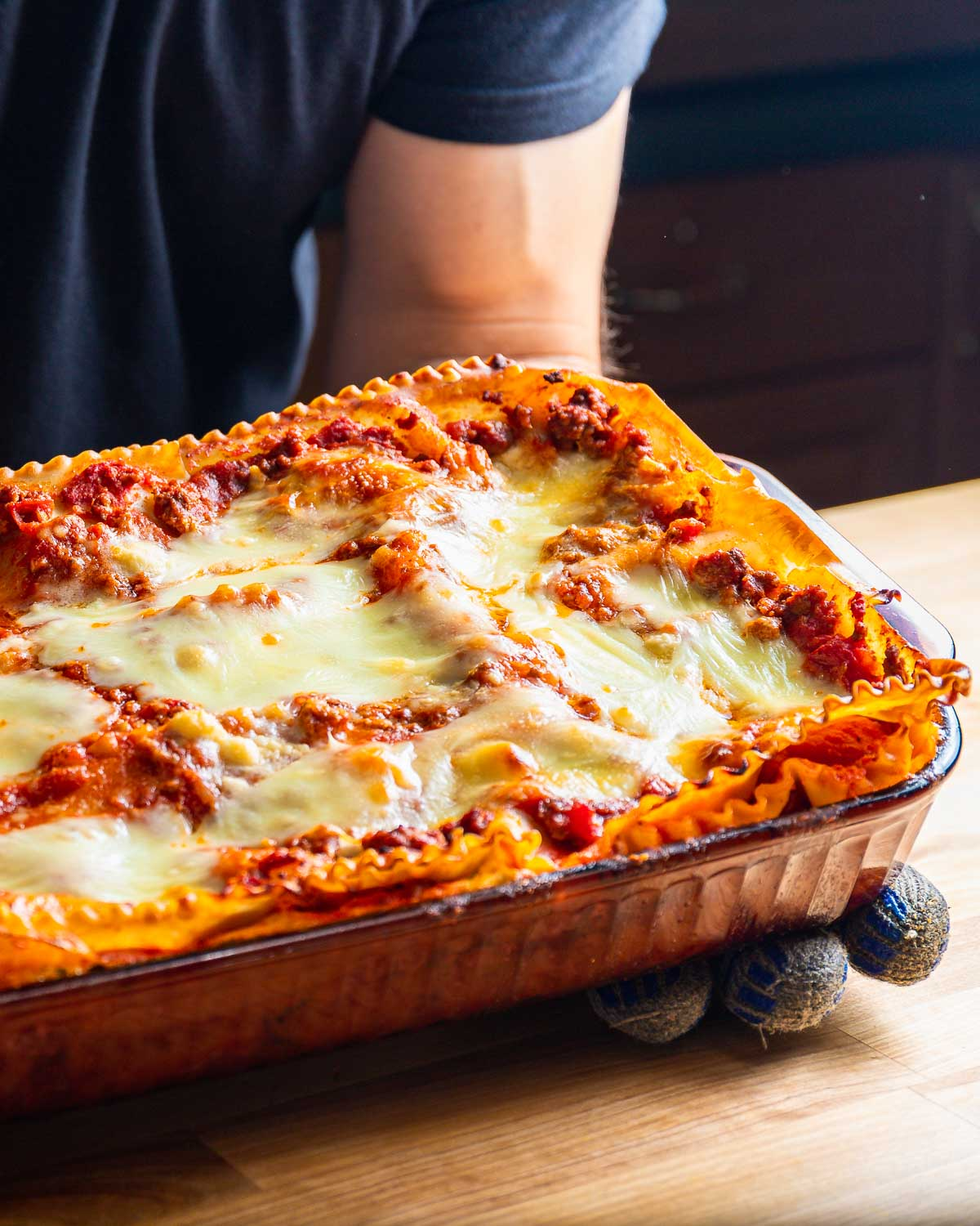 Lasagna in glass baking dish being held over table.