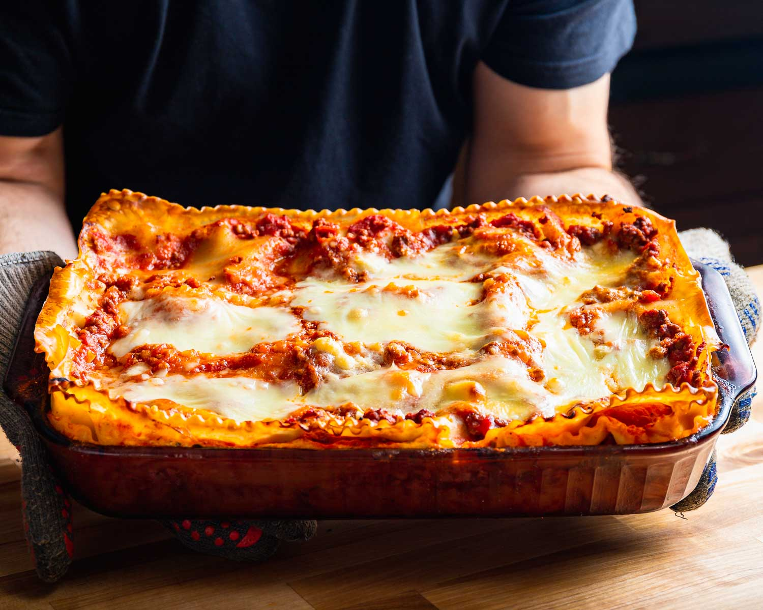 Tray of lasagna being held with gloves.