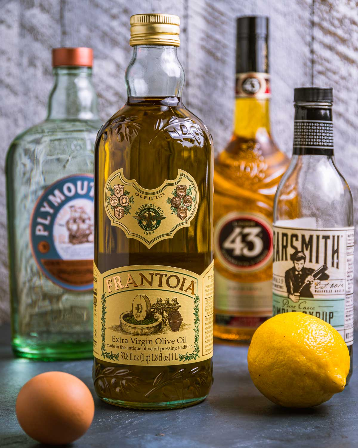 Ingredients shown: gin, olive oil, 43 liqueur, simple syrup, lemon, and egg.