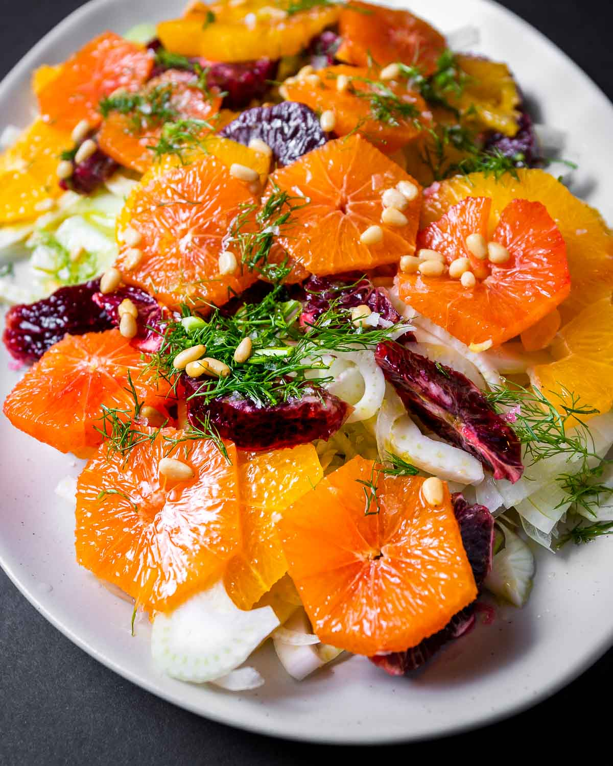 White platter with oranges, fennel, pine nuts, and fennel fronds.