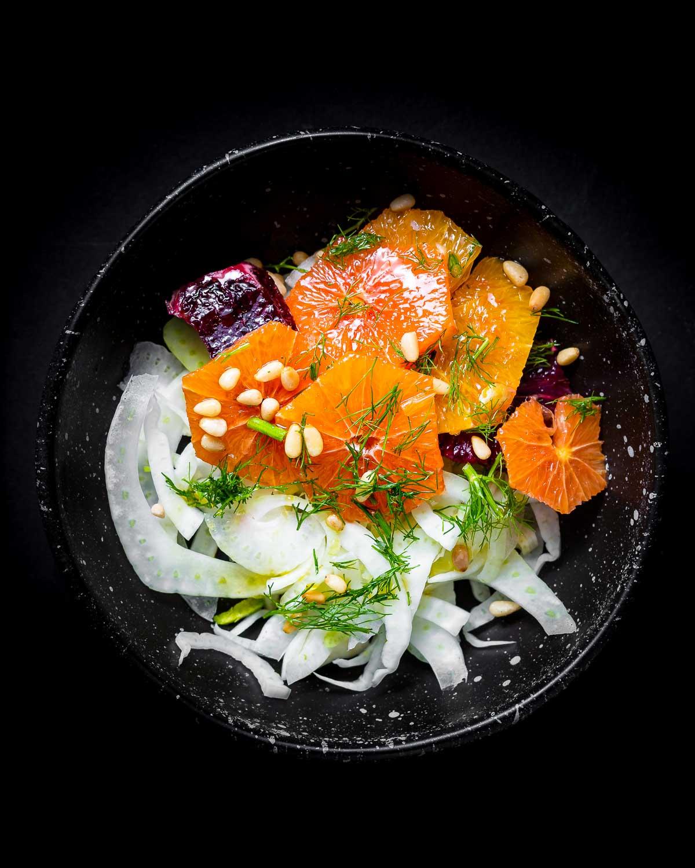 Black bowl of fennel and orange salad.