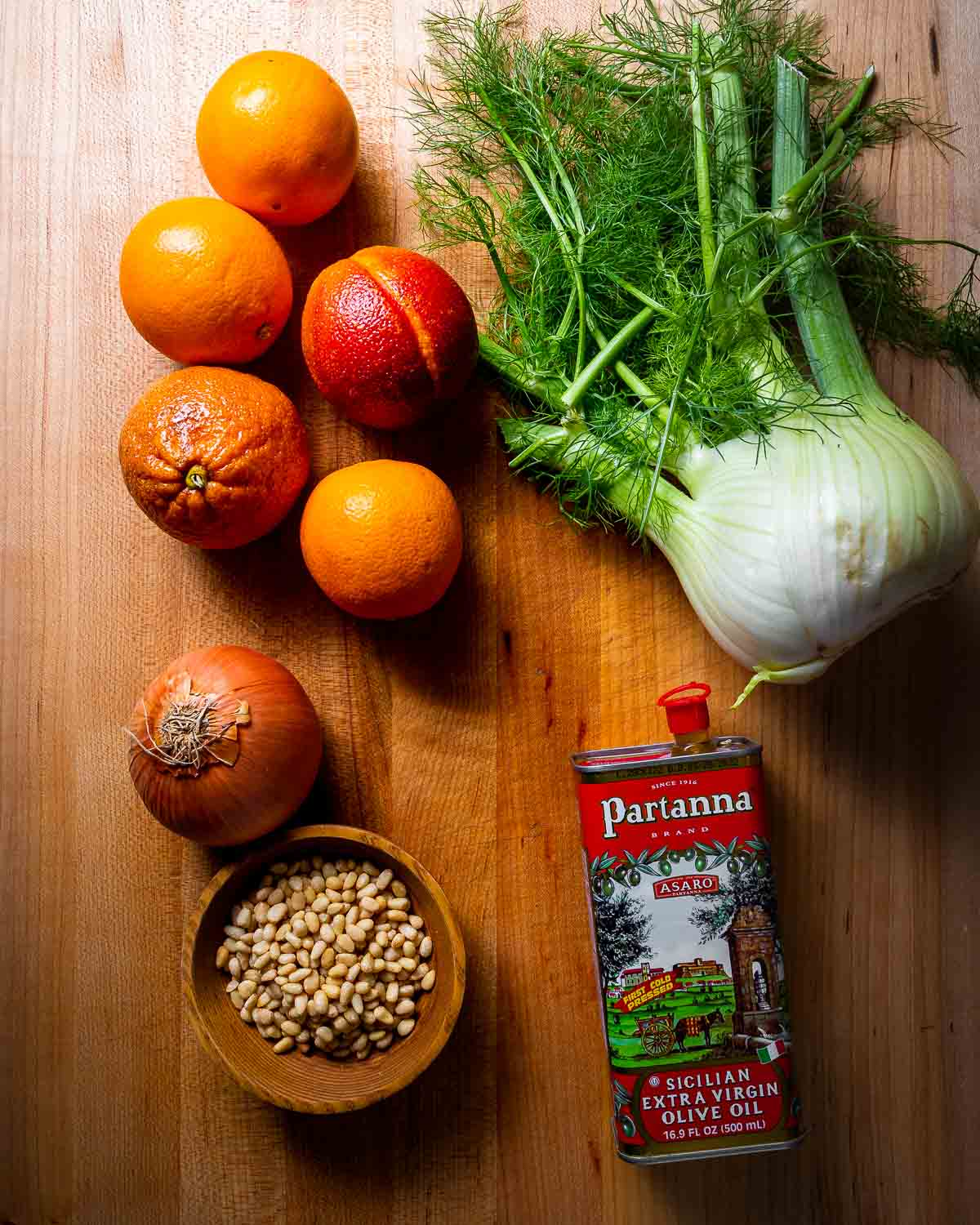 Ingredients shown: 5 oranges, 1 onion, 1 fennel, pine nuts and extra virgin olive oil on a wood cutting board.