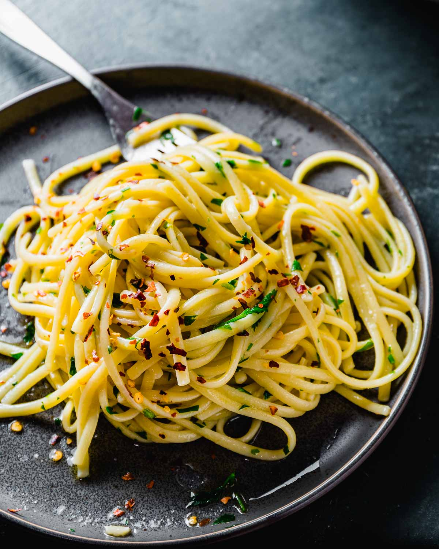Linguine aglio e olio in grey plate with fork.