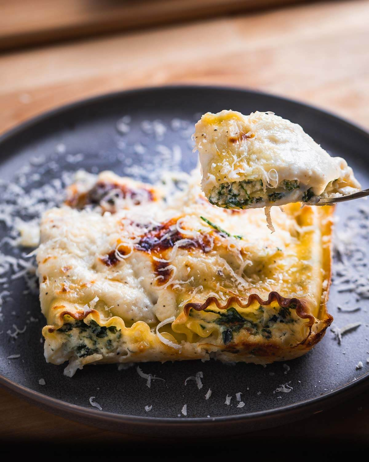 Cut piece of spinach lasagna roll up being held in fork.