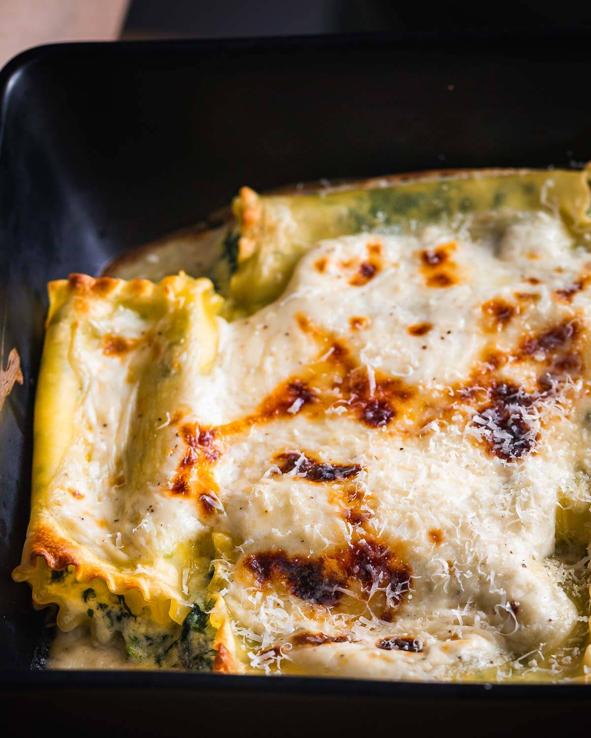 Spinach lasagna rolls with white sauce in black baking dish.