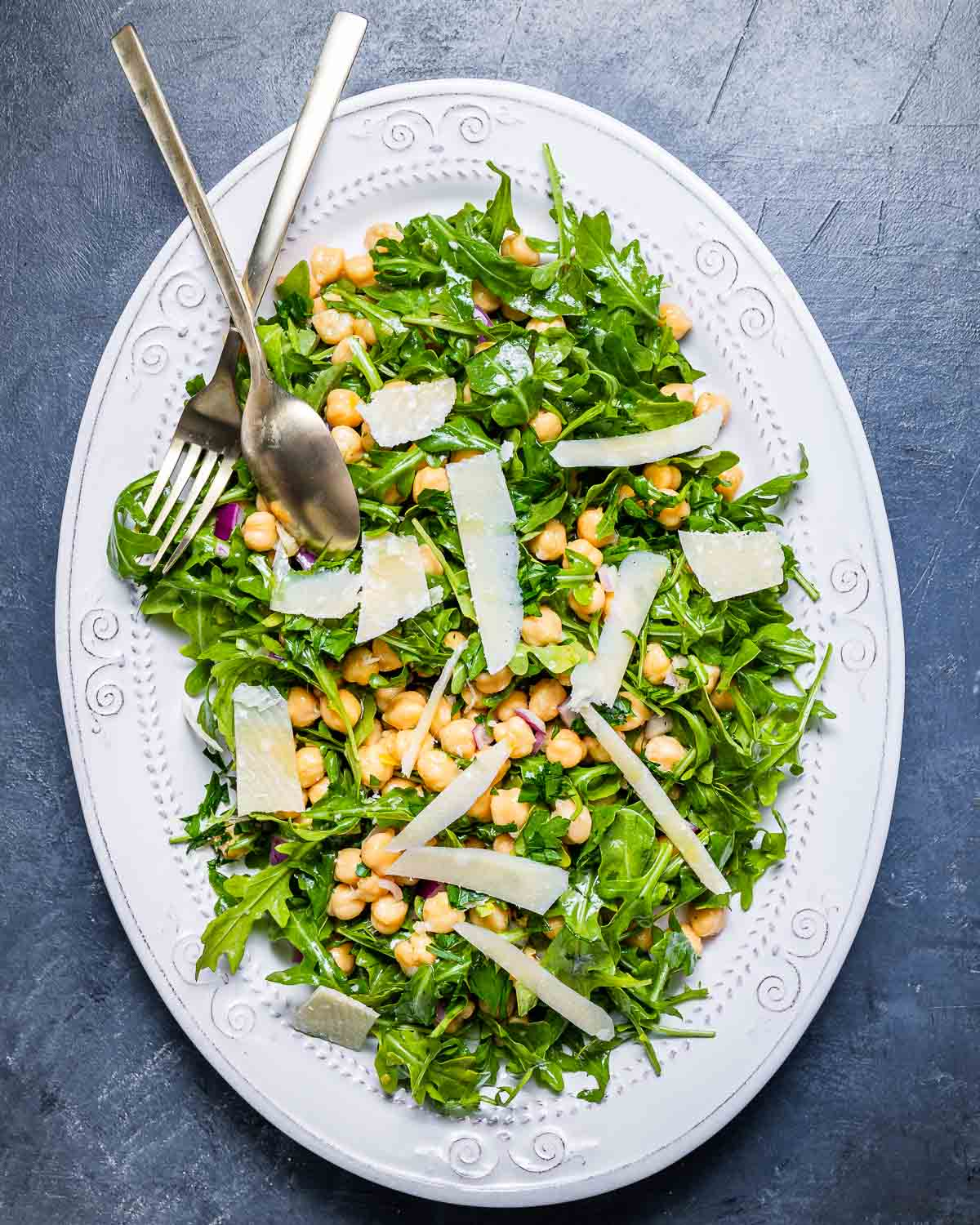 Overhead shot of white platter with arugula, chickpeas, and shaved cheese on blue board.