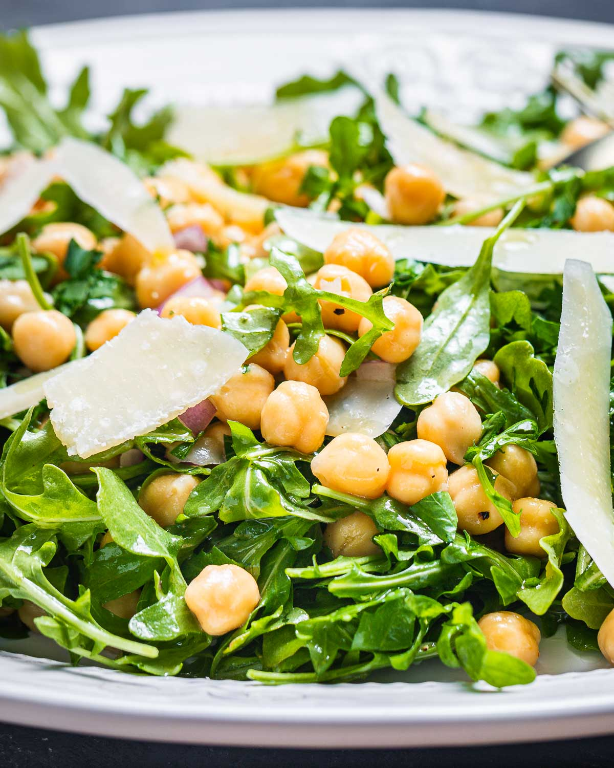 Large white platter of arugula with a few chickpeas and shaved parmesan cheese.