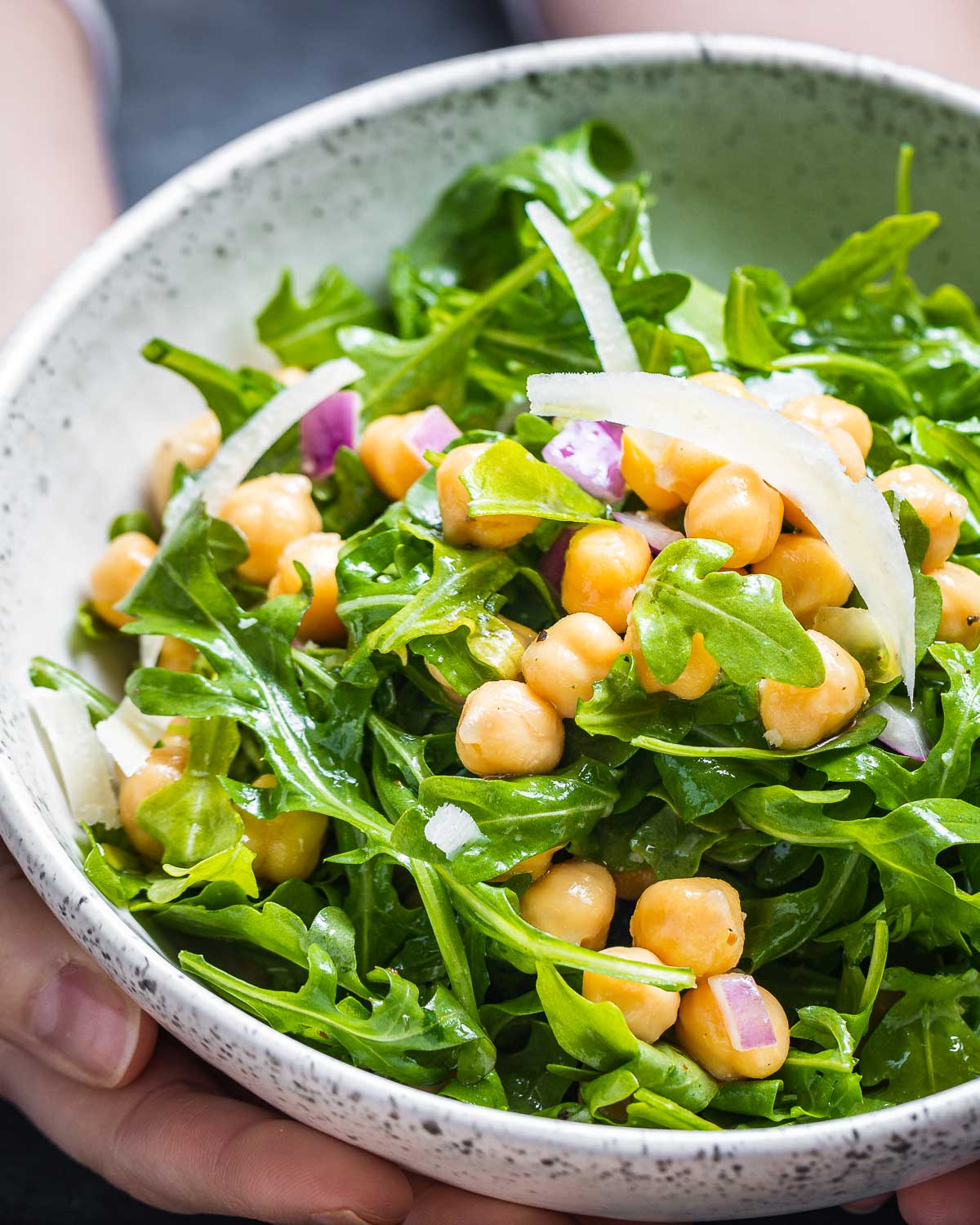 Arugula and chickpea salad being held in white bowl.