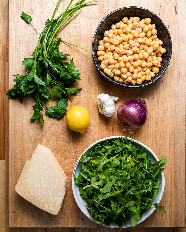 Ingredients shown: parsley, chickpeas, lemon, garlic, red onion, block of parmesan, and bowl of arugula.