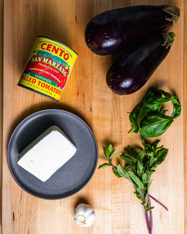 Ingredients shown: Can of plum tomatoes, 2 eggplants, ricotta salata, garlic, mint and basil.