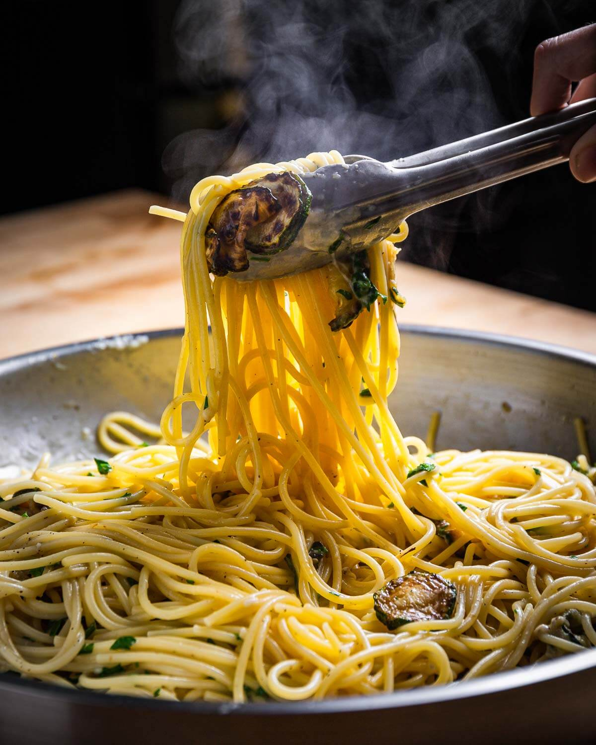Spaghetti being pulled out of pan and held in tongs.