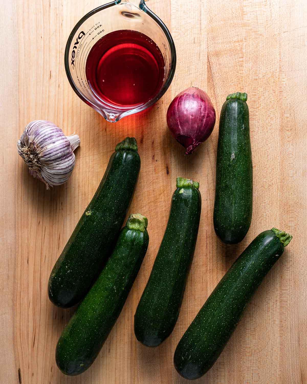 Ingredients shown: red wine vinegar, garlic, red onion, and 5 zucchini on cutting board.
