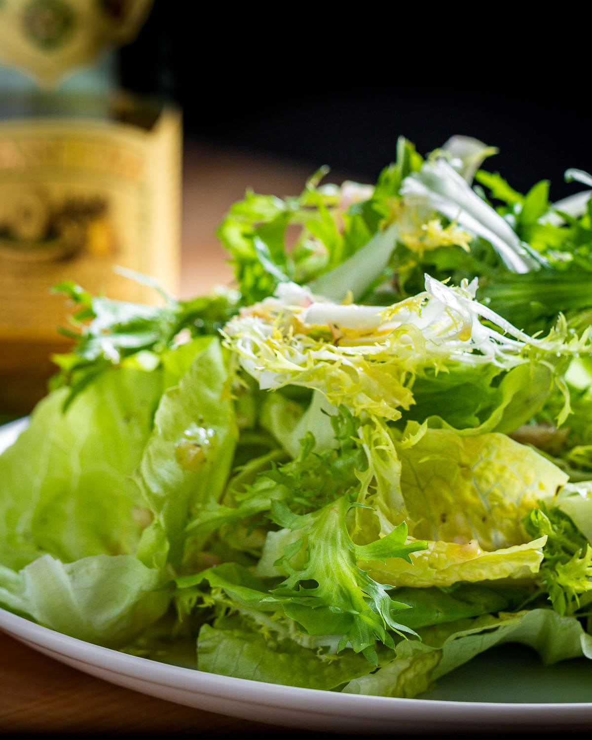 Plate of piled high lettuce greens with bottle of olive oil in background.